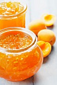 Apricot jam in jars on a wooden surface