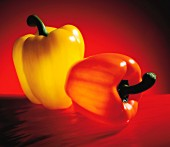 An orange and a yellow pepper on a red surface