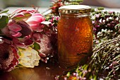 A jar of honey with honeycomb, surrounded by flowers