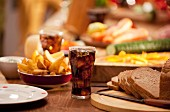 A table set with bread, potato wedges, raw vegetables and cola