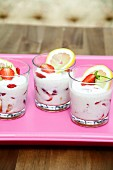 Yoghurt with fresh strawberries in dessert glasses on a tray