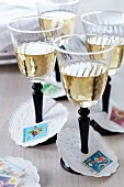 Paper collars decorated with postage stamps as wine glass drip catchers