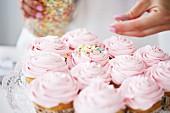 Woman decorating cupcakes with sugar sprinkles