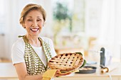 A woman proudly holding up a home-made pie