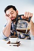 Mann sitzt noch fast schlafend am Tisch & verschüttet Kaffee