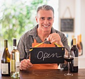 A man in a wine shop holding a sign saying 'Open'