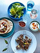 Souflaki skewers with pork, lemons and bay leaves served with tzatziki, tomato sauce, pita bread and salad