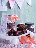 Dark chocolate brownies with a jar of ingredients and a recipe on a doily
