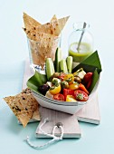 Greek salad in a cardboard dish served with lavash crisps