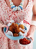 A woman holding a bowl of meatballs and spicy salsa for a party