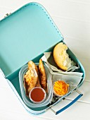 Teriyaki chicken with a dip, a bread roll and a carrot salad in a lunch box