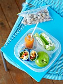 Wraps, cucumber, an apple and juice in a lunch box