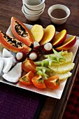 A dessert platter with fresh exotic fruits and lime syrup
