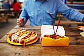 A man sitting at a wooden table with fast food and hot dogs