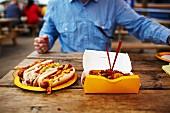 Mann sitzt an Holztisch vor Fast Food & Hot Dogs