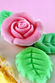 Sugar rose with leaves as decoration on a slice of cake