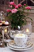 Gedeckter Tisch mit Kaffeegedeck, Gebäck & Blumen