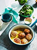 Lemon chicken meatballs in a saucepan with a mixed leaf salad and a mint dressing in the background