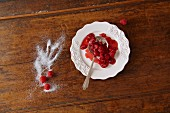 A Ladle with Raspberry Sauce on a White Plate; Fresh Raspberries and Sugar