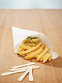 Chips with a sprig of rosemary in a cone of white baking parchment, and wooden chip forks