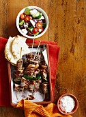 Beef skewers with bacon and courgette, served with a Greek salad