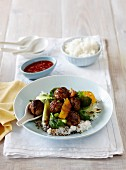 Fried meatballs with pak choi, oranges and rice (Asia)