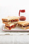 Sandwiches with beef steak, peppers, cheese and tomato sauce