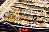 Courgette strips in an aluminium tray on a barbecue