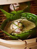 Green fish curry in a banana leaf bowl