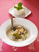 Asian coconut milk soup with chicken, vegetables and lime leaves