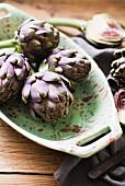 Fresh globe artichokes in a porcelain dish