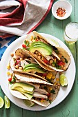 Tacos filled with chicken, chickpeas, sweetcorn and avocado