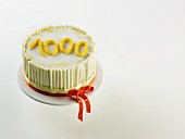 White anniversary cake with the figure '1000'