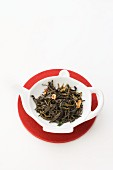 Tea leaves in a small dish shaped like a teapot