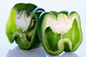Fresh green pepper sliced into 2 halves showing seeds