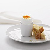A boiled egg in a white egg-cup with three fingers of lightly toasted bread