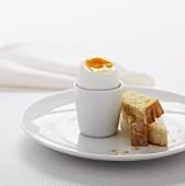 Gekochtes Ei im weißen Eierbecher und Toaststreifen