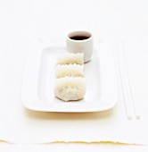 A white plate of three dumplings with a white ramekin of soy sauce dip