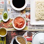 A variety of japanese ingredients in japanese crockery, on japanese newspaper