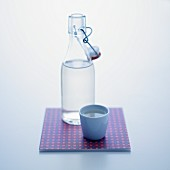 A stoppered bottle and a cup of water
