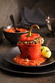 Peppers stuffed with minced meat and rice on a bed of tomato sauce