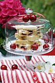 Cherry cake on glass cake stand with glass cover