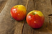 Two Lady Alice Apples on Wood