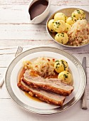 Crackling roast belly of pork, sliced and served with sauerkraut and potato dumplings