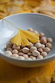 Gingko nuts and a yellow gingko leaf in a porcelain bowl