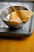 A gingko leaf in a silver bowl