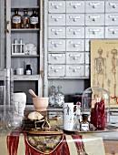 Mörser, Laborgläser, anatomische Abbildungen und Modelle des menschlichen Körpers vor altem, hellgrau lackiertem Apothekerschrank