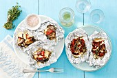 Two dishes grilled in foil: feta with dried tomatoes and eggplant with goat's cheese