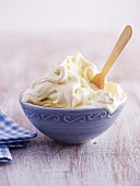 A bowl of melting vanilla ice cream with a wooden spoon