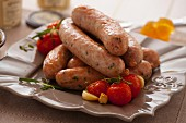 Oven-baked sausages with cherry tomatoes, garlic and thyme
